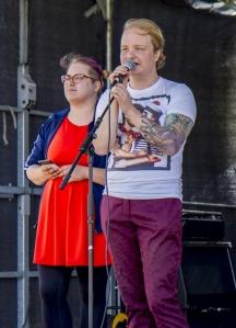 Kuvassa Panda Eriksson puhuu mikrofoniin lavalla. Hänellä on päällään tummanpunaiset housut ja valkoinen paita, missä seilori-printti