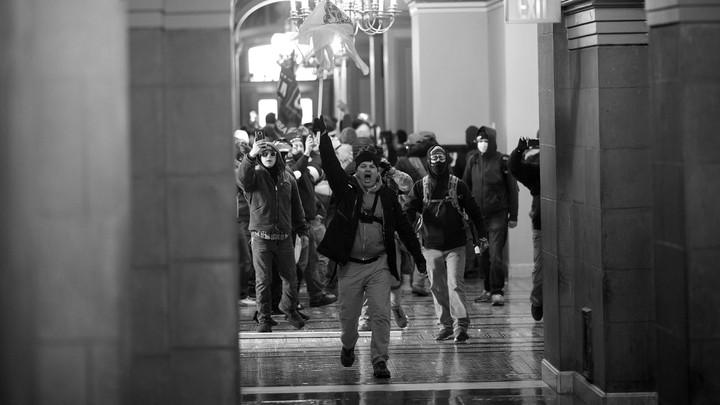 Pressikuva keskiviikon tapahtumista: iso ryhmä näennäisesti valkoisia miehiä ovat tunkeutuneet kongressirakennukseen.