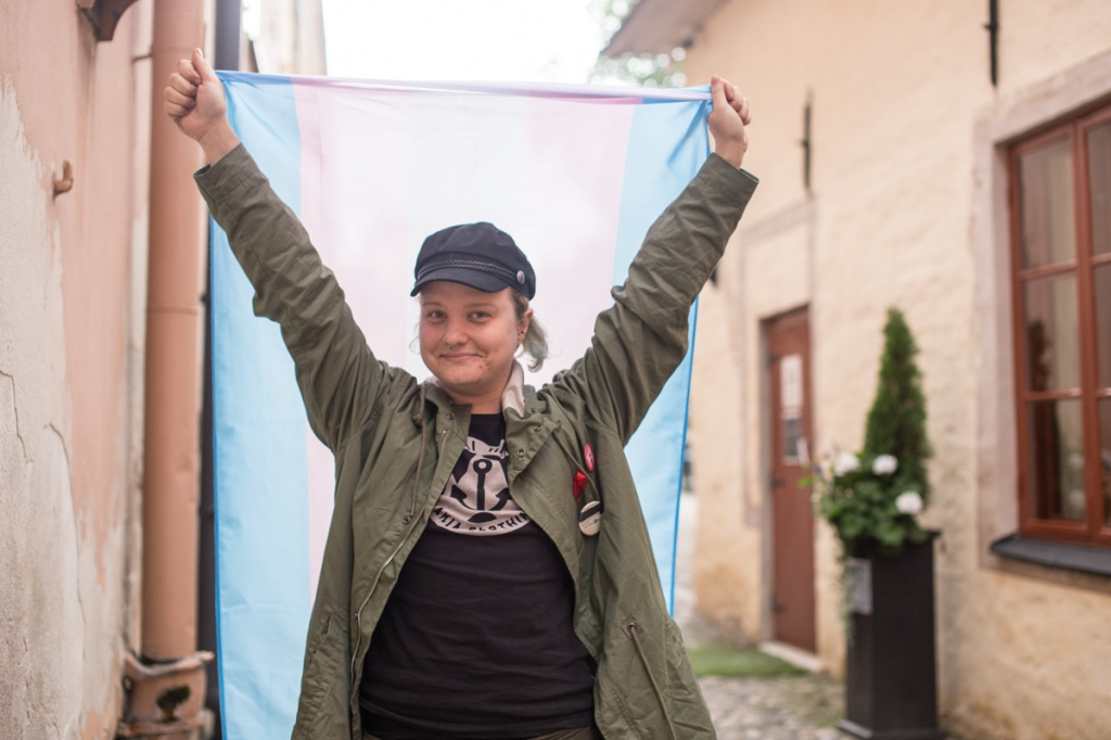 The picture features Panda Eriksson in a t-shirt, jacket and a black cap. They are holding up a trans flag and smiling toward the camera.